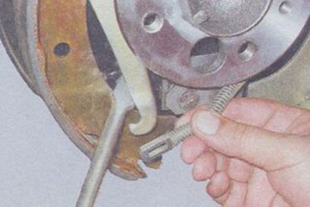 Отцепляем трос ручного тормоза от рычага тормозной колодки