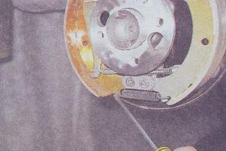 Снимаем нижнюю стяжную пружину задних тормозных колодок